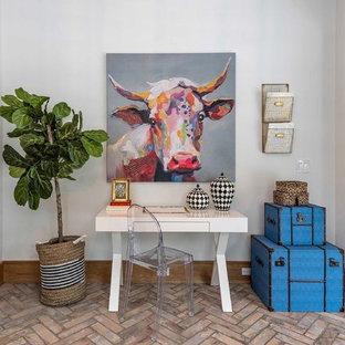 Immagine di un piccolo ufficio classico con pareti bianche, pavimento in mattoni, scrivania autoportante e nessun camino
