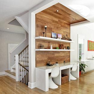 Modernes Arbeitszimmer mit Arbeitsplatz, braunem Holzboden und Einbau-Schreibtisch in New York