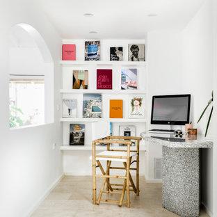 Bild på ett mellanstort funkis hemmastudio, med vita väggar, travertin golv, ett fristående skrivbord och beiget golv