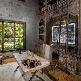 ロサンゼルスの巨大な地中海スタイルのおしゃれなホームオフィス・書斎 (ライブラリー、マルチカラーの壁、濃色無垢フローリング、自立型机、茶色い床) の写真