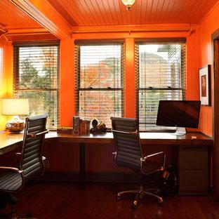 Ispirazione per uno studio design con pareti arancioni e parquet scuro