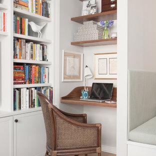 Exempel på ett litet klassiskt hemmabibliotek, med grå väggar, ljust trägolv, ett inbyggt skrivbord och beiget golv