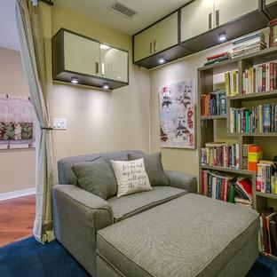 Immagine di un piccolo studio contemporaneo con libreria, pareti beige, moquette e pavimento blu
