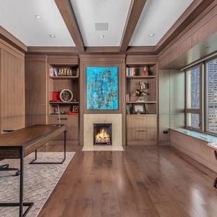 Idee per uno studio contemporaneo di medie dimensioni con libreria, camino classico, cornice del camino in pietra, scrivania autoportante e parquet scuro