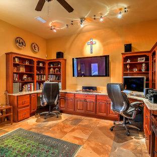 アルバカーキの広いサンタフェスタイルのおしゃれなホームオフィス・書斎 (黄色い壁、スレートの床、造り付け机、マルチカラーの床) の写真