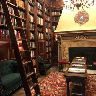 Mittelgroßes Klassisches Lesezimmer mit beiger Wandfarbe, braunem Holzboden, Kamin, Kaminumrandung aus Stein, freistehendem Schreibtisch und braunem Boden in Oklahoma City