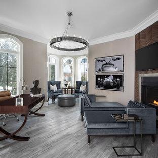 Exempel på ett stort klassiskt hemmastudio, med en standard öppen spis, en spiselkrans i trä, ett fristående skrivbord, beige väggar, ljust trägolv och grått golv