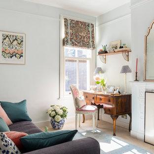 Klassisches Arbeitszimmer mit Arbeitsplatz, Teppichboden, Kamin und freistehendem Schreibtisch in London