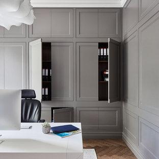 Inspiration för ett vintage hemmabibliotek, med grå väggar, mellanmörkt trägolv, ett fristående skrivbord och brunt golv