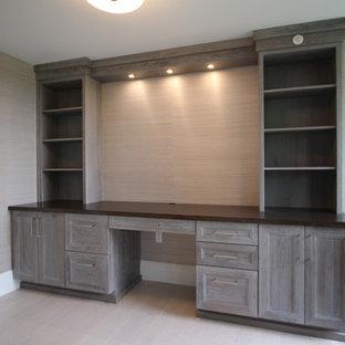 マイアミの中サイズのトラディショナルスタイルのおしゃれな書斎 (暖炉なし、グレーの壁、ラミネートの床、造り付け机、グレーの床) の写真