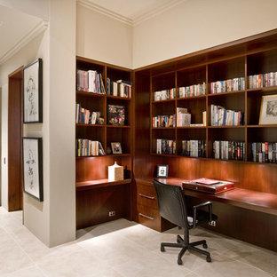 Bild på ett mellanstort funkis hemmabibliotek, med beige väggar, travertin golv och ett inbyggt skrivbord