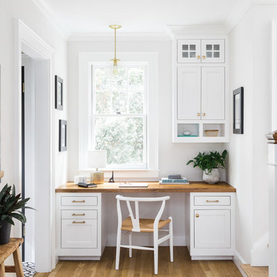 Study room - small traditional built-in desk light wood floor study room idea in Boston with white walls