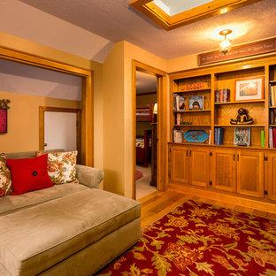 Immagine di un ufficio country di medie dimensioni con pareti gialle e pavimento in legno massello medio