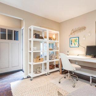 ロサンゼルスの小さいエクレクティックスタイルのおしゃれな書斎 (白い壁、ラミネートの床、自立型机、茶色い床) の写真