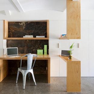 Immagine di un ufficio scandinavo di medie dimensioni con pareti bianche, pavimento in cemento e scrivania incassata