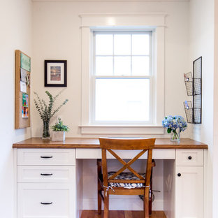 Example of a coastal built-in desk medium tone wood floor and brown floor home office design in New York with white walls