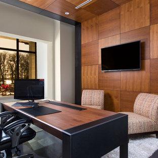 Inspiration för stora moderna hemmabibliotek, med vita väggar, klinkergolv i porslin, ett fristående skrivbord och grått golv