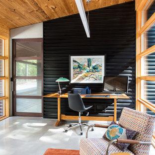 Idéer för ett mellanstort lantligt hemmabibliotek, med svarta väggar, ett fristående skrivbord, betonggolv och grått golv