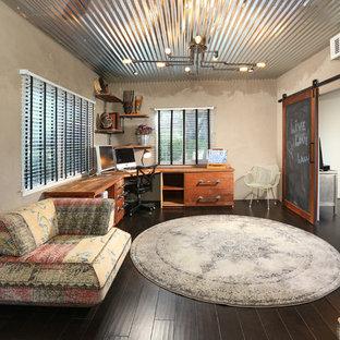 Inspiration för ett stort industriellt hemmabibliotek, med ett fristående skrivbord, mörkt trägolv, grå väggar och brunt golv