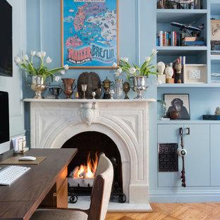 Foto di un piccolo studio boho chic con libreria, pareti blu, pavimento in legno massello medio, camino classico, cornice del camino in pietra, scrivania autoportante e pavimento marrone