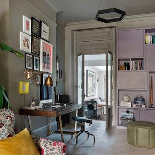 Inredning av ett eklektiskt litet hemmabibliotek, med grå väggar, ljust trägolv och ett fristående skrivbord