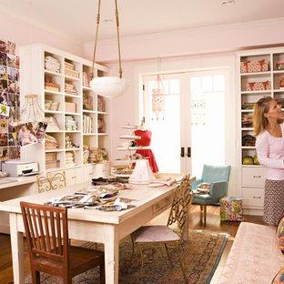 Foto på ett eklektiskt hemmastudio, med rosa väggar, mellanmörkt trägolv och ett inbyggt skrivbord
