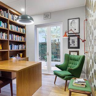 Foto de despacho bohemio con paredes grises, suelo de madera clara, escritorio empotrado y suelo beige