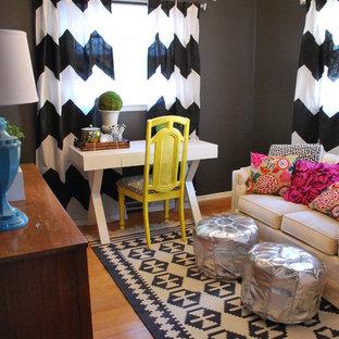 Idéer för ett eklektiskt arbetsrum, med svarta väggar, mellanmörkt trägolv och ett fristående skrivbord
