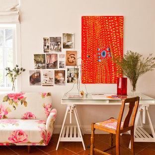 На фото: кабинет в стиле фьюжн с белыми стенами, полом из терракотовой плитки и отдельно стоящим рабочим столом