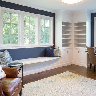 Idee per un ampio studio chic con libreria, pareti blu, parquet scuro, camino bifacciale, cornice del camino in mattoni e scrivania incassata