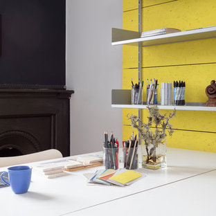 This is an example of a medium sized contemporary home studio in Edinburgh with yellow walls, light hardwood flooring, a corner fireplace, a metal fireplace surround and a freestanding desk.