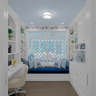 Idéer för mellanstora vintage hemmabibliotek, med vita väggar, mellanmörkt trägolv, ett inbyggt skrivbord och brunt golv