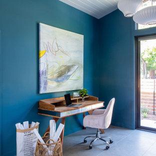 Inspiration för stora retro hemmabibliotek, med blå väggar, klinkergolv i porslin, ett fristående skrivbord och grått golv