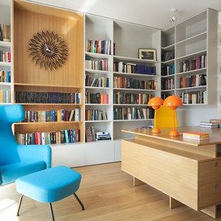 他の地域のコンテンポラリースタイルのおしゃれなホームオフィス・書斎 (ライブラリー、マルチカラーの壁、無垢フローリング、造り付け机、黄色い床) の写真
