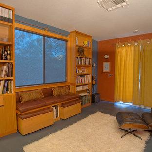 Esempio di un piccolo atelier moderno con pareti arancioni, pavimento in cemento e scrivania autoportante