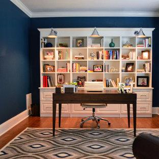 オーランドの小さいビーチスタイルのおしゃれなホームオフィス・書斎 (ライブラリー、青い壁、無垢フローリング、自立型机、茶色い床) の写真