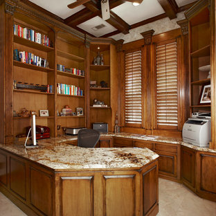 This is an example of a large traditional study in Dallas with beige walls, limestone flooring, no fireplace and a built-in desk.