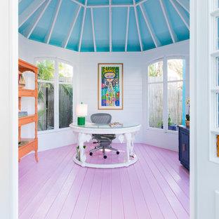 Diseño de despacho tropical con paredes blancas, suelo de madera pintada, escritorio independiente y suelo rosa