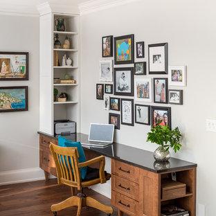 Ejemplo de despacho clásico con paredes grises, suelo de madera en tonos medios y escritorio empotrado