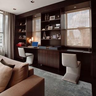 Cette image montre un petit bureau minimaliste avec un mur marron, un sol en bois foncé, une cheminée ribbon, un manteau de cheminée en métal, un bureau intégré et un sol marron.