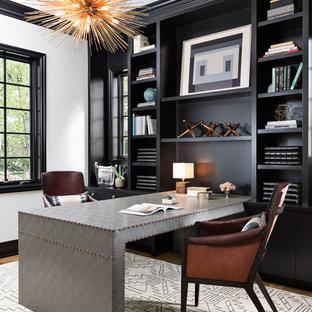 デトロイトの広いトランジショナルスタイルのおしゃれなホームオフィス・書斎 (ライブラリー、造り付け机、黒い壁、無垢フローリング、茶色い床) の写真