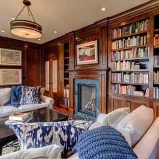 Exempel på ett mellanstort klassiskt hemmabibliotek, med bruna väggar, mellanmörkt trägolv, en standard öppen spis och en spiselkrans i sten