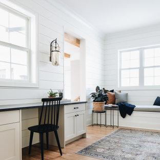 Idéer för lantliga hemmabibliotek, med vita väggar, mellanmörkt trägolv, ett inbyggt skrivbord och brunt golv