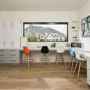 ソルトレイクシティの巨大なコンテンポラリースタイルのおしゃれな書斎 (白い壁、淡色無垢フローリング、造り付け机、ベージュの床) の写真
