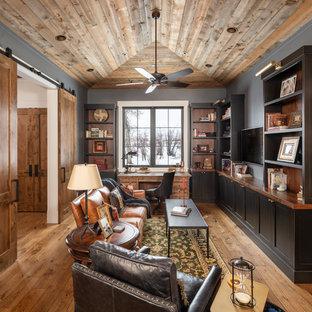 Свежая идея для дизайна: кабинет в стиле кантри с серыми стенами, паркетным полом среднего тона, отдельно стоящим рабочим столом и коричневым полом - отличное фото интерьера
