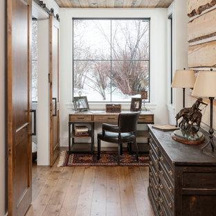 Country Arbeitszimmer mit weißer Wandfarbe, braunem Holzboden, freistehendem Schreibtisch und braunem Boden in Salt Lake City