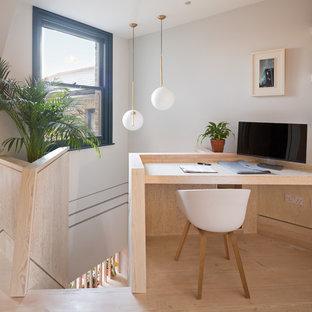 ロンドンの中サイズのコンテンポラリースタイルのおしゃれなホームオフィス・書斎 (マルチカラーの壁、合板フローリング、造り付け机、茶色い床) の写真