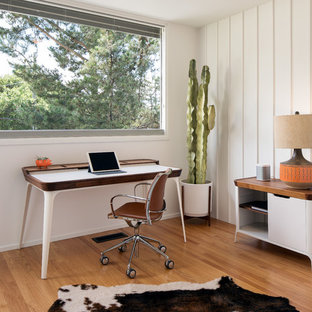 Small 1960s freestanding desk medium tone wood floor and brown floor study room photo in San Francisco with white walls