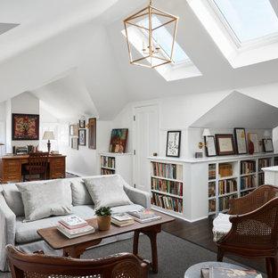 Inspiration för stora klassiska hemmabibliotek, med vita väggar, mörkt trägolv, ett fristående skrivbord, brunt golv och en standard öppen spis