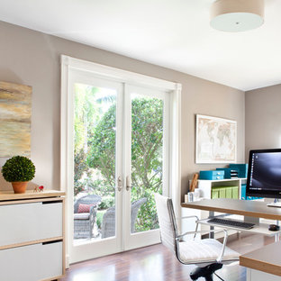 Study room - mid-sized transitional built-in desk dark wood floor study room idea in Miami with beige walls